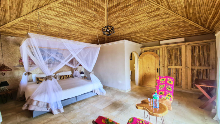 A double bed and a table with two chairs in one of the delta-view lodges at Hotel Les Palétuviers