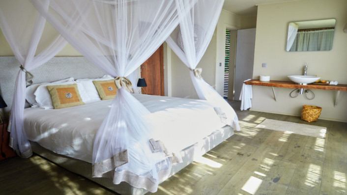 A double bed and a sink in the water suite at Hotel Les Palétuviers