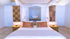 A double bed and two night lights in one of the garden suites of one of the garden suites of Hotel Les Palétuviers