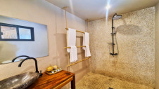 A shower, a sink and towels in the bathroom of one of the lodges with delta view at Hotel Les Palétuviers