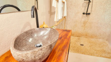 A sink and a shower in one of the family suites at Hotel Les Palétuviers