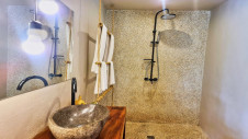 Towels, a sink and a shower in the bathroom of one of the lodges overlooking the garden of Hotel Les Palétuviers