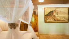 A double bed and a painting of a lion in one of the zebra lodges at Hotel Les Palétuviers